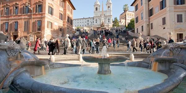 Fountain on Spanish square with Spanish Steps on background